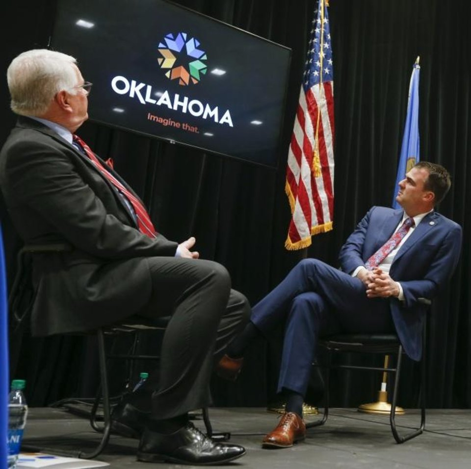 Photo -  Steve Hendrickson, left, director of government affairs for Boeing, and Gov. Kevin Stitt watch a video during the unveiling of the new brand for Oklahoma. [Nate Billings/The Oklahoman]