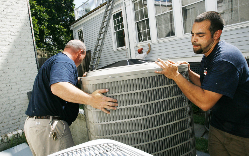 FILE- In this Monday June 9, 2008, file photo, Charles Brinkley, left, and John Lerro, with Great American Heating and Air Conditioning, Inc., install an air conditioner in Chevy Chase, Md. A sharp decline in the price of natural gas makes it much cheaper for U.S. utilities to produce electricity. It just isn\'t having any impact on homeowners\' monthly bills. Instead of falling, electricity prices aren\'t budging. They are rising just as families begin cranking up their air conditioners. (AP Photo/Jacquelyn Martin, File) ORG XMIT: NYBZ106