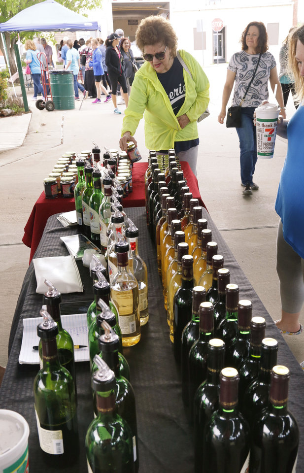 Photo -  Phonda Curl looks at jellies and wines from Wildhorse Canyon Farms on opening day of the Edmond Farmers Market. [PHOTO BY PAUL HELLSTERN, THE OKLAHOMAN]