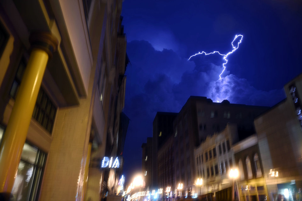 Photo - Lightning strikes over downtown in Knoxville, Tenn., on Sunday, July 27, 2014. Authorities say powerful storms crossing east Tennessee have destroyed at least 10 homes and damaged others. (AP Photo/The Knoxville News Sentinel, Saul Young)