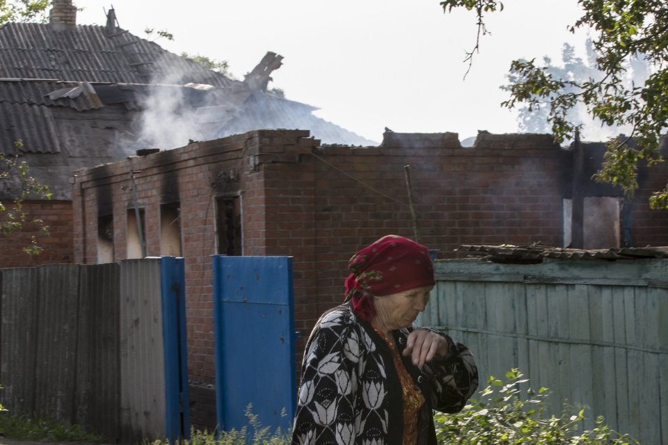Photo - An elderly local woman passes a house destroyed by shellings in Semyonovka village, outside Slovyansk, Ukraine, Friday, May 23, 2014. The village on the outskirts of Slovyansk, a city which has been the epicenter of clashes for weeks, has seen continuous shelling by the Ukrainian government forces, who have retaliated to the rebel fire. On Friday, a private house was destroyed by mortar fire that came from the Ukrainian side. There were no casualties, as the family living there had left the previous day, according to local residents. (AP Photo/Alexander Zemlianichenko)