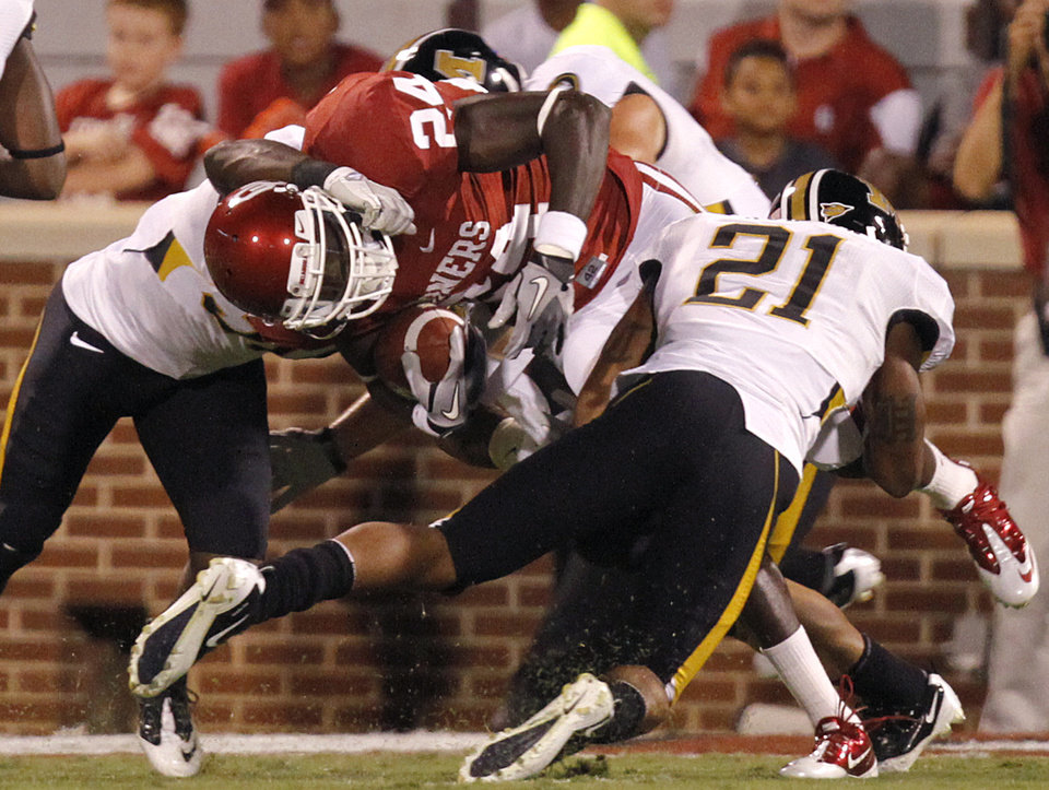 Oklahoma's Dejuan Miller (24) is brought down by Missouri's Trey Hobson (21) during their game Saturday in Norman.Photo by Chris Landsberger, The Oklahoman