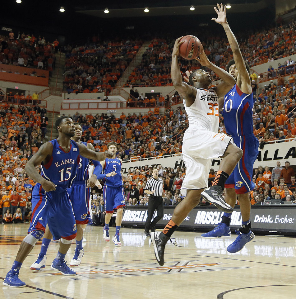 Photo - Oklahoma State 's Marcus Smart (33) drives against Kansas' Kevin Young (40) during the college basketball game between the Oklahoma State University Cowboys (OSU) and the University of Kanas Jayhawks (KU) at Gallagher-Iba Arena on Wednesday, Feb. 20, 2013, in Stillwater, Okla. Photo by Chris Landsberger, The Oklahoman