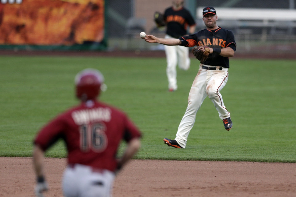 Photo - San Francisco Giants shortstop Brandon Hicks, right, makes the throw to first in time to get the out on Arizona Diamondbacks' Chris Owings, left, during the ninth inning of a spring exhibition baseball game on Sunday, March 2, 2014, in Scottsdale, Ariz. (AP Photo/Gregory Bull)