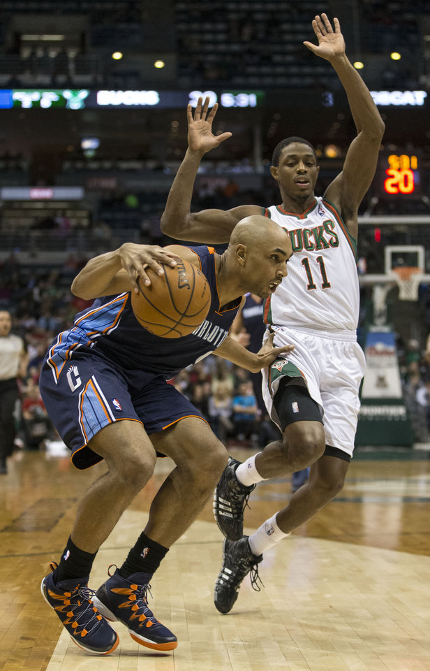 Photo - Milwaukee Bucks' Brandon Knight, right, is called for a foul while trying to defend against Charlotte Bobcats' Gerald Henderson during the first half of an NBA basketball game on Sunday, March 16, 2014, in Milwaukee. (AP Photo/Tom Lynn)