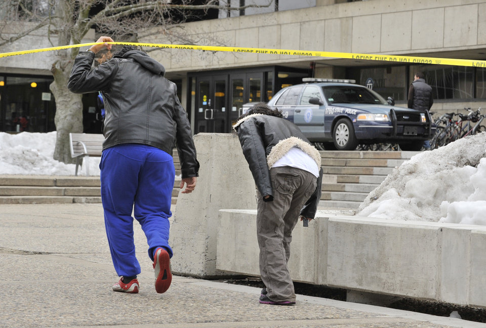 Pedestrians on the MIT Campus in Cambridge, Mass., duck underneath police tape, Saturday, Feb. 23, 2013, after police responded to reports of a gunman on campus that Cambridge police later said were unfounded.  Police said that officers searched for a man reported to be carrying a long rifle and wearing body armor and found nothing. A spokeswoman for the university says the school also called off a campus-wide lockdown. (AP Photo/Josh Reynolds)
