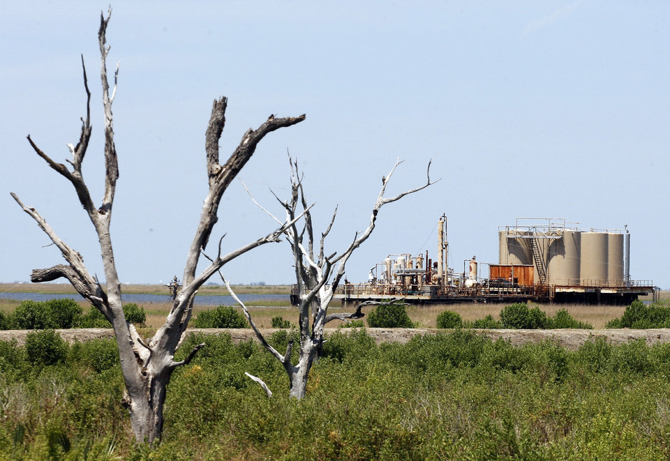 Photo - FILE -In this May 10, 2010 photo, an oil facility stands past dead trees on Isle de Jean Charles, La.  Global warming is rapidly turning America into a stormy and dangerous place, with rising seas and disasters upending lives from flood-stricken Florida to the wildfire-ravaged West, according to a new U.S. federal scientific report released Tuesday, May 6, 2014. (AP Photo/Patrick Semansky, File)