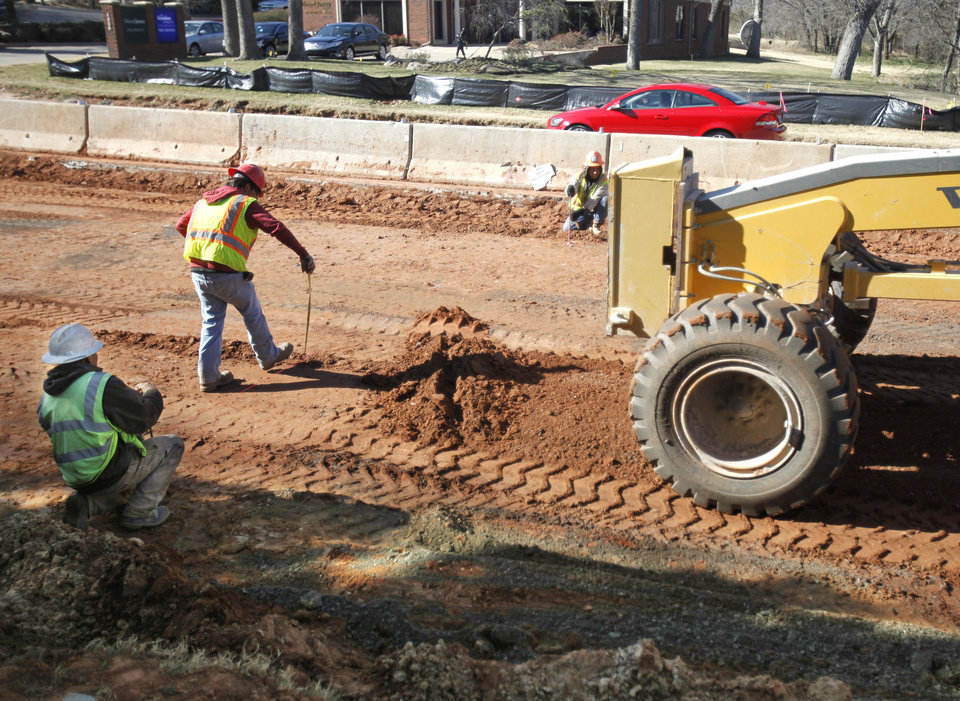 Workers continue preparing the base for the Bryant Avenue bridge replacement project in Edmond. Asphalt base work is expected to be completed this week on the east side of the roadway. One lane of traffic is open on Bryant Avenue just south of 15th Avenue. PHOTO BY PAUL HELLSTERN, THE OKLAHOMAN <strong>PAUL HELLSTERN - THE OKLAHOMAN</strong>