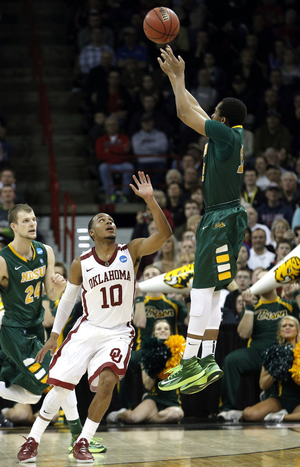 Photo - North Dakota State's Lawrence Alexander (12) shoots a three-pointer to send the game into overtime as Oklahoma's Jordan Woodard defends during the NCAA men's basketball tournament game between the University of Oklahoma and North Dakota State at the Spokane Arena in Spokane, Wash., Thursday, March 20, 2014. Oklahoma home lost 80-75. Photo by Sarah Phipps, The Oklahoman