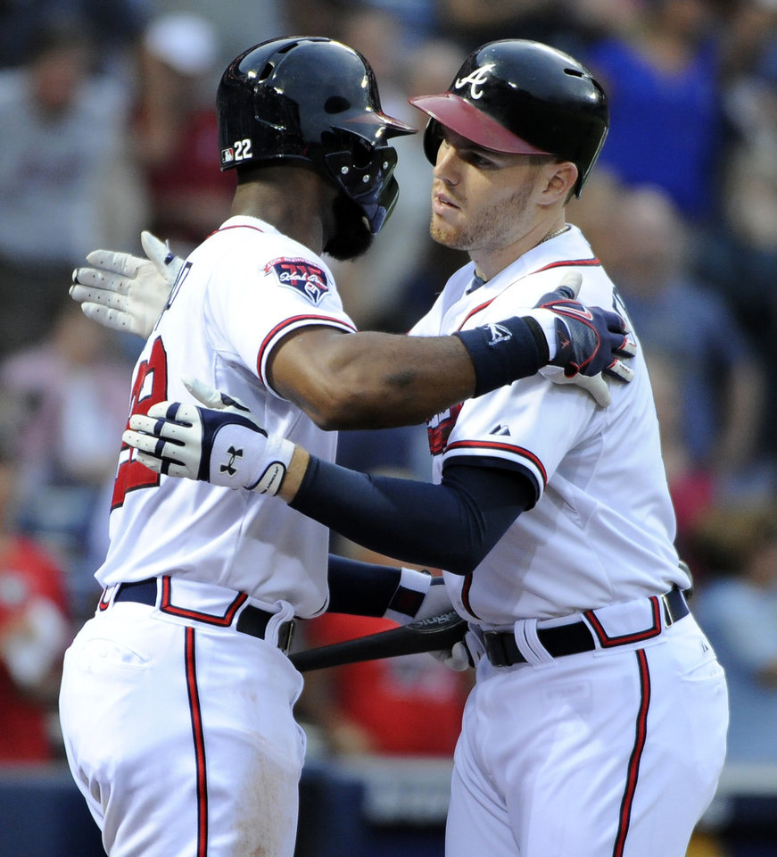 Photo - Atlanta Braves' Freddie Freeman, right, is congratulated at home plate by Jason Heyward after Freeman's two-run home run against the Washington Nationals during the second inning of a baseball game Friday, Aug. 8, 2014, in Atlanta. (AP Photo/David Tulis)