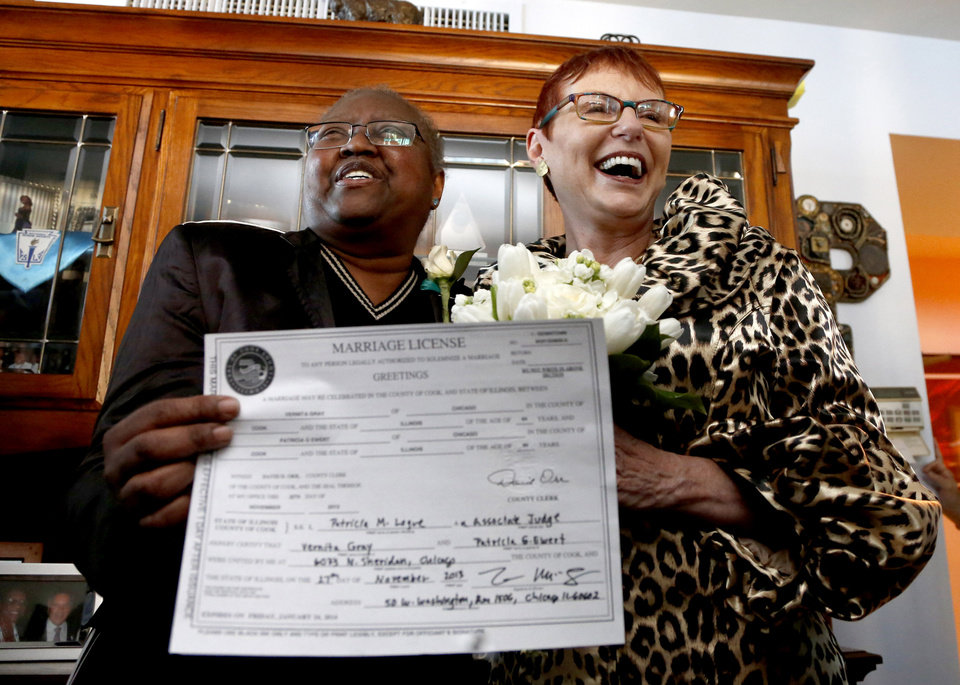 Photo - ADVANCE FOR USE SUNDAY, DEC. 22 AND THEREAFTER - FILE - In this Nov. 27, 2013 file photo, Vernita Gray, left, and Patricia Ewert smile at friends after they were married in Chicago by Cook County Judge Patricia Logue, the first gay marriage in Illinois. A judge ordered the Cook County clerk to issue an expedited marriage license to Gray and Ewert before the state's gay marriage law takes effect in June 2014, because Gray is terminally ill. The story on the Illinois General Assembly approving the gay-marriage bill was voted as one of the top 10 stories in the state for 2013.  (AP Photo/Charles Rex Arbogast, File)