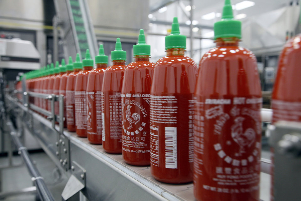 Photo - FILE - In the Tuesday, Oct. 29, 2013, file photo, Sriracha chili sauce is produced at the Huy Fong Foods factory in Irwindale, Calif. A Texas lawmaker is making a pitch to move Sriracha hot sauce production to his state from a plant in Irwindale, California, where some residents' complaints about its smell have led to city action. (AP Photo/Nick Ut, File)