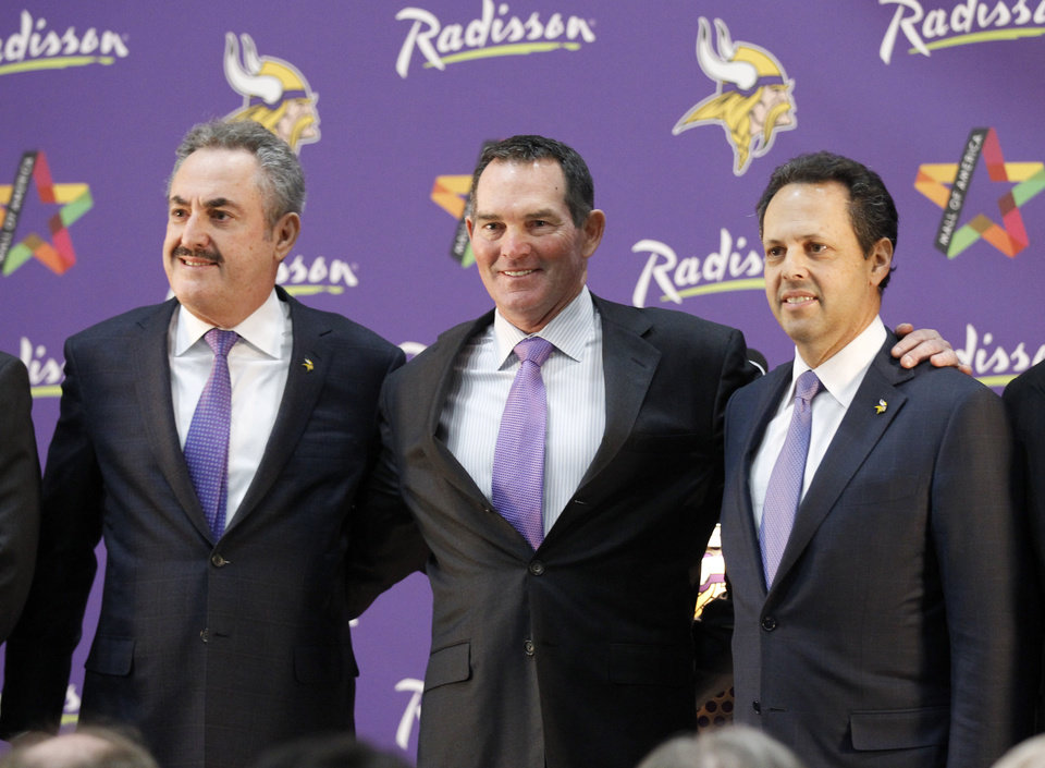 Photo - New Minnesota Vikings head coach Mike Zimmer, center, poses with team owner Zygi Wilf, left, and Mark Wilf, right, during an NFL football media availability at Winter Park in Eden Prairie, Minn., Friday, Jan. 17, 2014. Zimmer is the ninth head coach in the Vikings' franchise history.(AP Photo/Ann Heisenfelt)