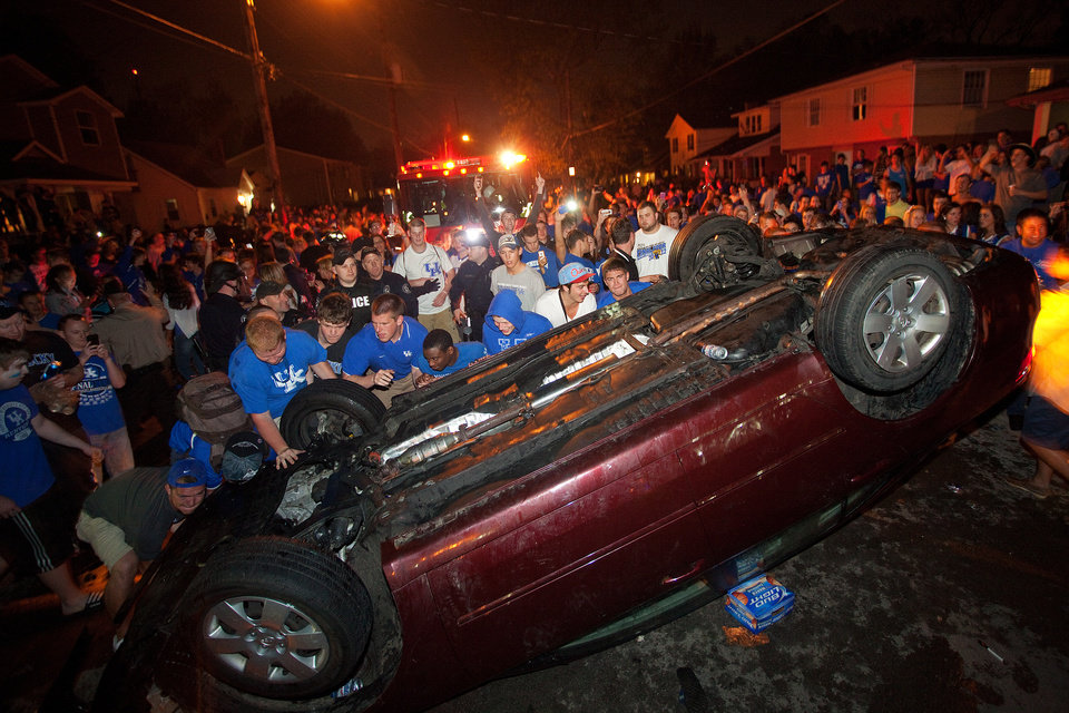 Kentucky fans flip a car on State Street as they celebrate Kentucky's 69-61 win over Louisville in an NCAA Final Four semifinal college basketball tournament game, Saturday, March 31, 2012, in Lexington, Ky. (AP Photo/The Lexington Herald-Leader, Jonathan Palmer)