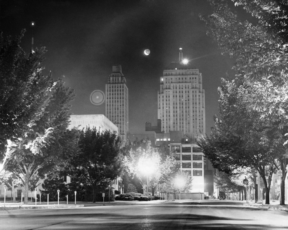 OKLAHOMA CITY / SKY LINE / OKLAHOMA / NIGHT SCENES:  Sleepy City Gets Rare View of Astronomical Tricks - Nope, you don't have spots before your eyes.  And it's not an eclipse of the moon - it's just an interesting picture of Oklahoma City's nocturnal appearance.  If you slept a little late Tuesday - say until about 5 a.m. - you missed the above sight.  The photographer snapped it at 4:10 a.m. Tuesday, catching the moon and the shadows directly between the First National and Liberty National Bank buildings.  The big spot at the left of the Liberty National is a light reflection he says - no trickery, scout's honor.  This picture was made looking east from Municipal Auditorium.  Staff photo by C.J. Kaho.  Photo dated 05/20/1952 and published 05/20/1952 in The Oklahoma City Times.