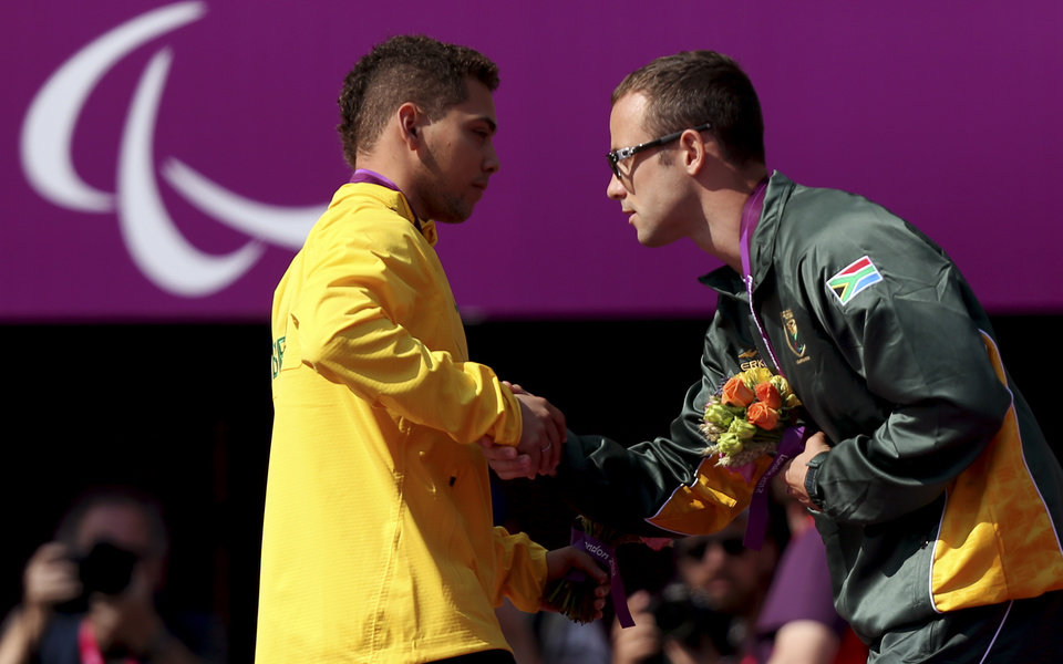 Photo -   Gold medal winner Brazil's Alan Oliveira, left, shakes hands with silver medalist South Africa's Oscar Pistorius during the medal ceremony for the men's 200m T44 category final during the athletics competition at the 2012 Paralympics, Monday, Sept. 3, 2012, in London. Pistorius, who won a legal battle to compete wearing carbon-fiber blades alongside able-bodied runners at the Olympics last month, suggested after the race that Oliveira ran with longer prosthesis than should be allowed. (AP Photo)