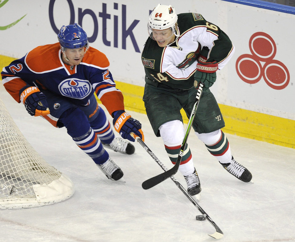 Photo - Edmonton Oilers' Jeff Petry, left, defends against Minnesota Wild's Mikael Granlund during first period NHL hockey game action in Edmonton, Alberta, on Tuesday, April 16, 2013.  (AP Photo/The Canadian Press, John Ulan)