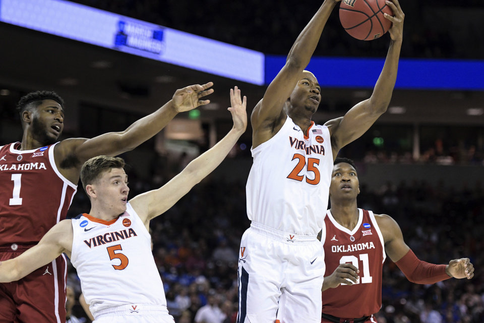 Photo - Virginia's Mamadi Diakite (25) and Kyle Guy (5) compete for a rebound against Oklahoma's Rashard Odomes (1) and Kristian Doolittle (21) during the first half of a second-round game in the NCAA men's college basketball tournament Sunday, March 24, 2019, in Columbia, S.C. (AP Photo/Sean Rayford)