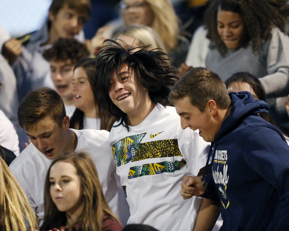 Photo - Kingfisher fans jump around during a high school football game between Perkins-Tryon and Kingfisher in Kingfisher, Okla., Thursday, Oct. 17, 2019. [Nate Billings/The Oklahoman]