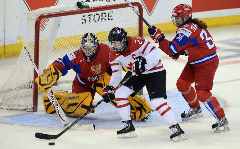 Photo - FILE - In this April 8, 2013, file photo, Canada's Hayley Wickenheiser, center, attempts to score on Russia's Anna Prugova as Svetlana Tkachyova defends during the first period of their semifinal game in the women's world hockey championship in Ottawa, Ontario. Since women's ice hockey became an Olympic sport in Nagano in 1998, the Canada and the United States have dominated the podium, winning every gold medal and all but one of the silvers. (AP Photo/The Canadian Press, Sean Kilpatrick, File)