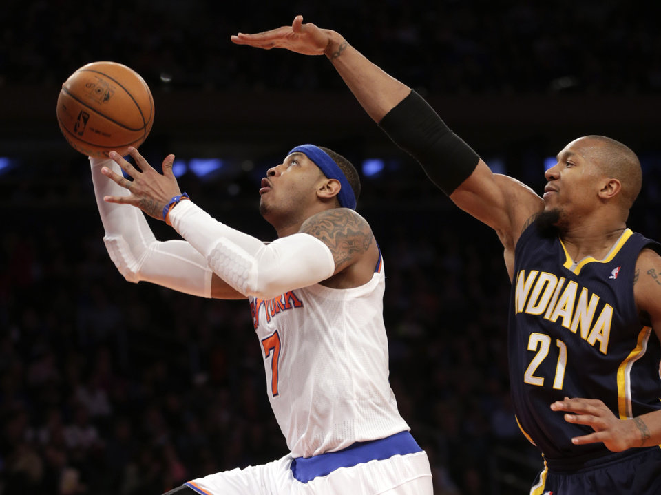 Photo - New York Knicks' Carmelo Anthony, left, shoots past Indiana Pacers' David West during the second half of the NBA basketball game, Sunday, April 14, 2013, in New York. The Knicks won 90-80. (AP Photo/Seth Wenig)