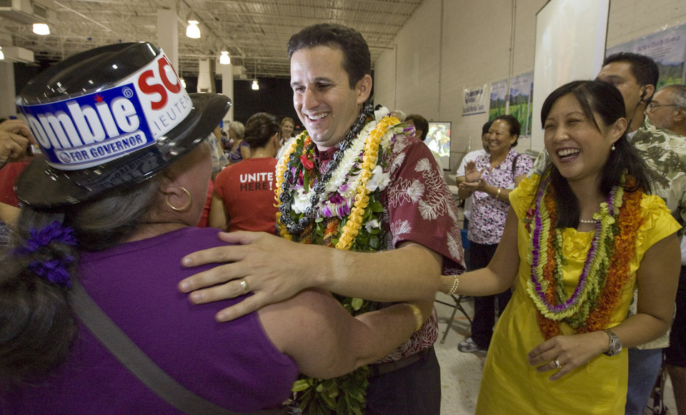 Photo - FILE- In this Nov. 3, 2010 file photo, a supporter congratulates then-Lt. governor-elect Brian Schatz, center, as his wife Linda looks on at the Neil Abercrombie-Brian Schatz Hawaii governor's post election party in Honolulu. Schatz was appointed by Gov. Neil Abercrombie Wednesday, Dec. 26, 2012 to succeed the late U.S. Sen. Daniel Inouye. (AP Photo/Eugene Tanner, File)