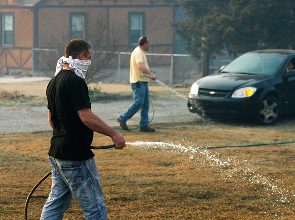 Photo - David Kinsey, 30, hoses down the yard of his father-in-law, Jerry Hunter, background, at 20089 NE 23rd Friday, March 11, 2011. Photo by Jim Beckel, The Oklahoman