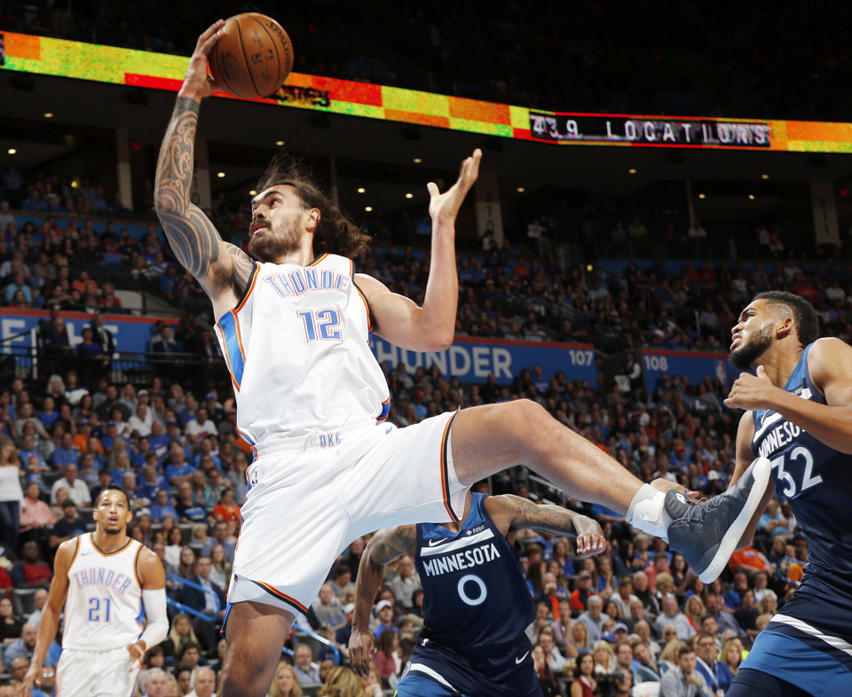 Photo - Oklahoma City's Steven Adams (12) grabs a rebound in front of Minnesota's Karl-Anthony Towns (32) during an NBA basketball game between the Oklahoma City Thunder and the Minnesota Timberwolves at Chesapeake Energy Arena in Oklahoma City, Sunday, Oct. 22, 2017. Photo by Nate Billings, The Oklahoman