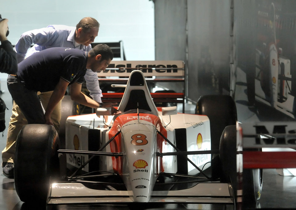 Photo - Technicians checks a Mc Laren Formula One car driven by Ayrton Senna, on display at the the Imola track, Italy, Wednesday, April 30, 2014. Fans and family members are gathering this week to pay their respects to former Formula One drivers Ayrton Senna and Roland Ratzenberger on the 20th anniversary of their deaths. F1 drivers' chaplain Sergio Mantovani celebrated a memorial mass Wednesday in a packed room beside pit lane at the Enzo and Dino Ferrari track that once hosted the San Marino Grand Prix. (AP Photo/Marco Vasini)