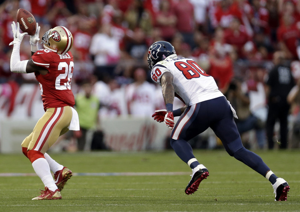Photo - San Francisco 49ers cornerback Tramaine Brock, left, intercepts a pass intended for Houston Texans wide receiver Andre Johnson, right, in the first half of an NFL football game in San Francisco, Sunday, Oct. 6, 2013. (AP Photo/Marcio Jose Sanchez)