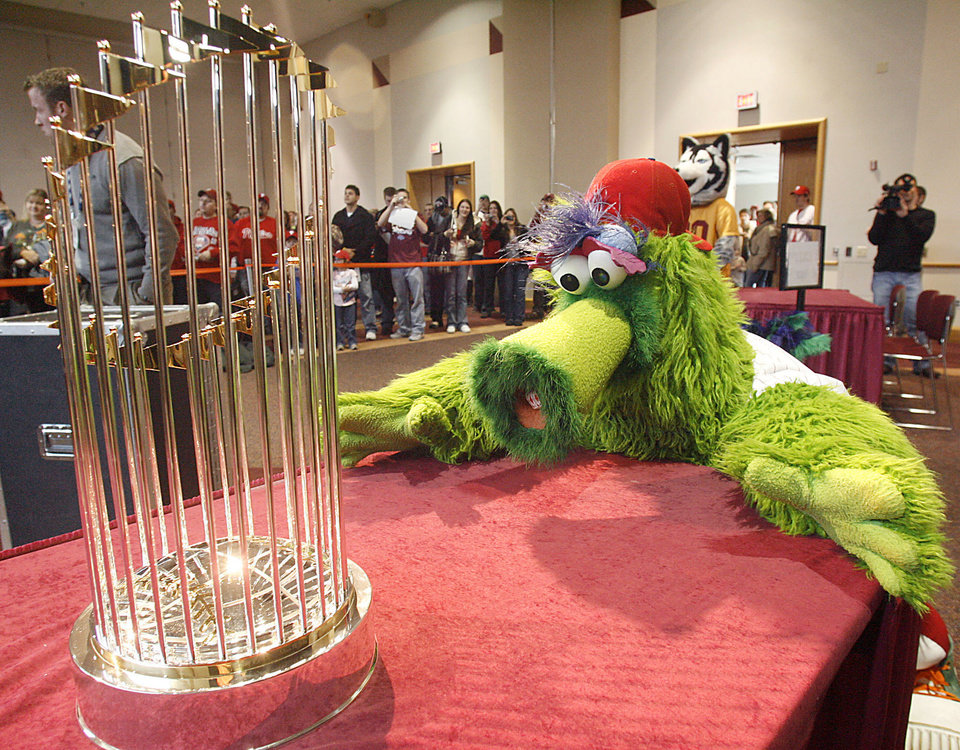 Photo - MASCOT: The Phillie Phanatic eyes up the location of the 2008 World Series Trophy Friday afternoon, Jan. 23, 2009, inside of the Kehr Union on the campus of Bloomsburg University, Bloomsburg, Pa., as the trophy is set on display. The Commissioner's Trophy is on a tour through out the Phillies' fan base area giving them a chance to have their pictures take with the trophy and the Phillie Phanatic. (AP Photo/Bloomsburg Press Enterprise, Jimmy May) ORG XMIT: PABLO102