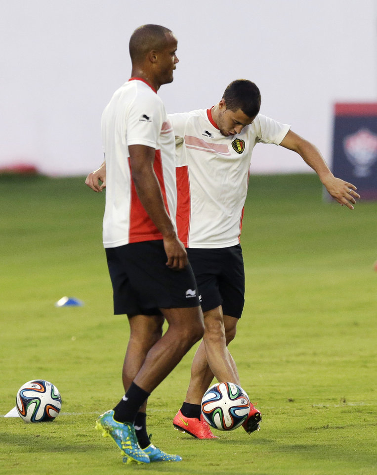 Photo - Belgium's captain Vincent Kompany, left, who is recovering from an injury, takes part in a training session as Eden Hazard flicks a ball at Estadio Manoel Barradas, the day before the World Cup round of 16 soccer match between Belgium and USA at Arena Fonte Nova in Salvador, Brazil, Monday, June 30, 2014. (AP Photo/Matt Dunham)