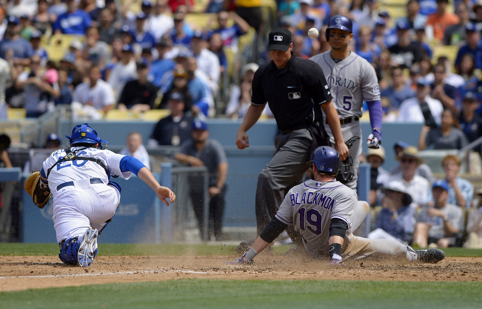 Photo - Colorado Rockies' Charlie Blackmon, lower right, scores after Brandon Barnes was caught stealing second as the ball goes past Los Angeles Dodgers catcher Tim Federowicz, left, while home plate umpire Stu Scheurwater and Rockies' Carlos Gonzalez look on during the fifth inning of a baseball game, Sunday, April 27, 2014, in Los Angeles. (AP Photo/Mark J. Terrill)