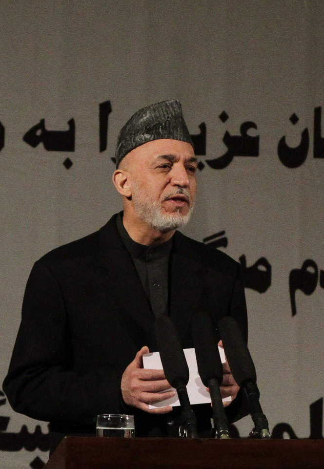 Photo - Afghan President Hamid Karzai delivers a nationally televised speech about the state of Afghan women in Kabul, Afghanistan, Sunday, March, 10, 2013. Karzai on Sunday accused the Taliban and the U.S. of working in concert to convince Afghans that violence will worsen if most foreign troops leave as planned by the end of next year. Karzai says two deadly suicide bombings on Saturday show the insurgent group is conducting attacks to help show that international forces will still be needed to keep the peace after their current combat mission ends in 2014. (AP Photo/Ahmad Jamshid)