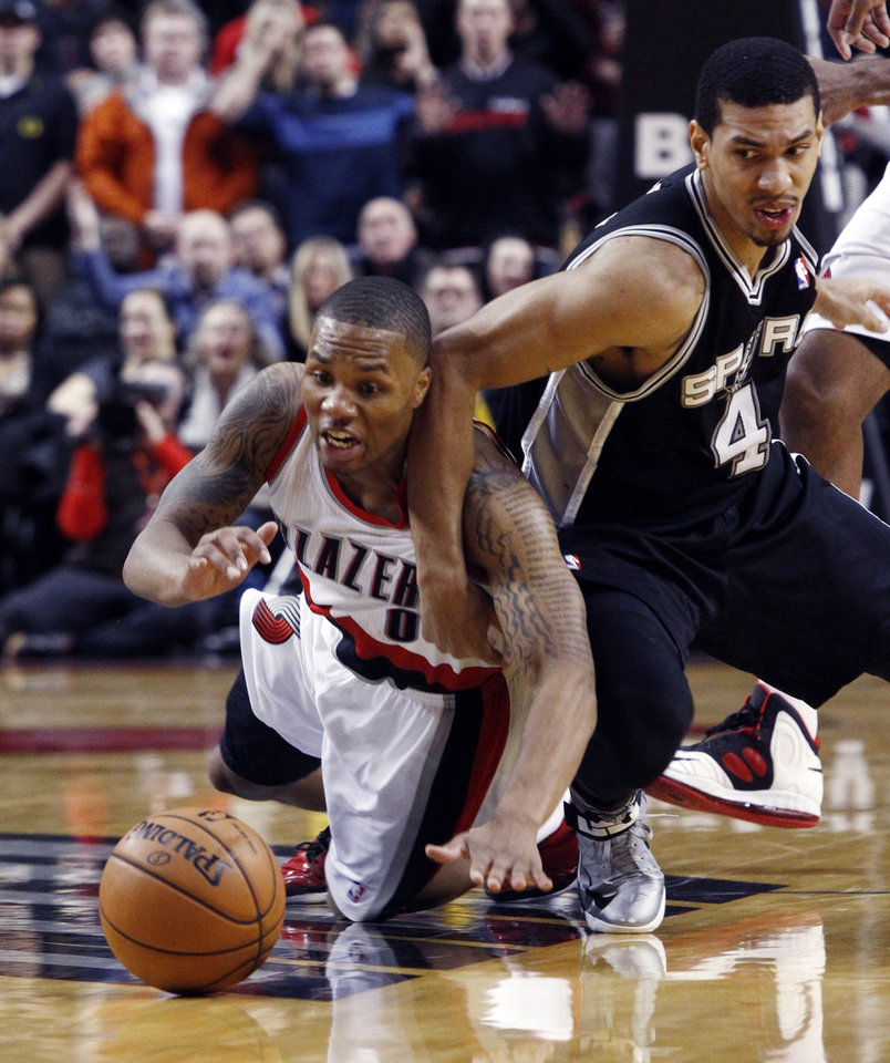 Photo - FILE- In this Dec. 13, 2012, file photo, Portland Trail Blazers guard Damian Lillard, left, battles for a loose ball with San Antonio Spurs forward Danny Green during the second half of an NBA basketball game in Portland, Ore.  The Trail Blazers are expected to announce Lillard as the league's Rookie of the Year on Wednesday, May 1, 2013. (AP Photo/Don Ryan, File)