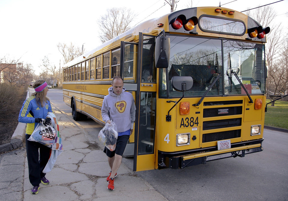 Photo - Runners in the 118th Boston Marathon disembark a bus as they arrive near the start line Monday, April 21, 2014 in Hopkinton, Mass. (AP Photo/Stephan Savoia)