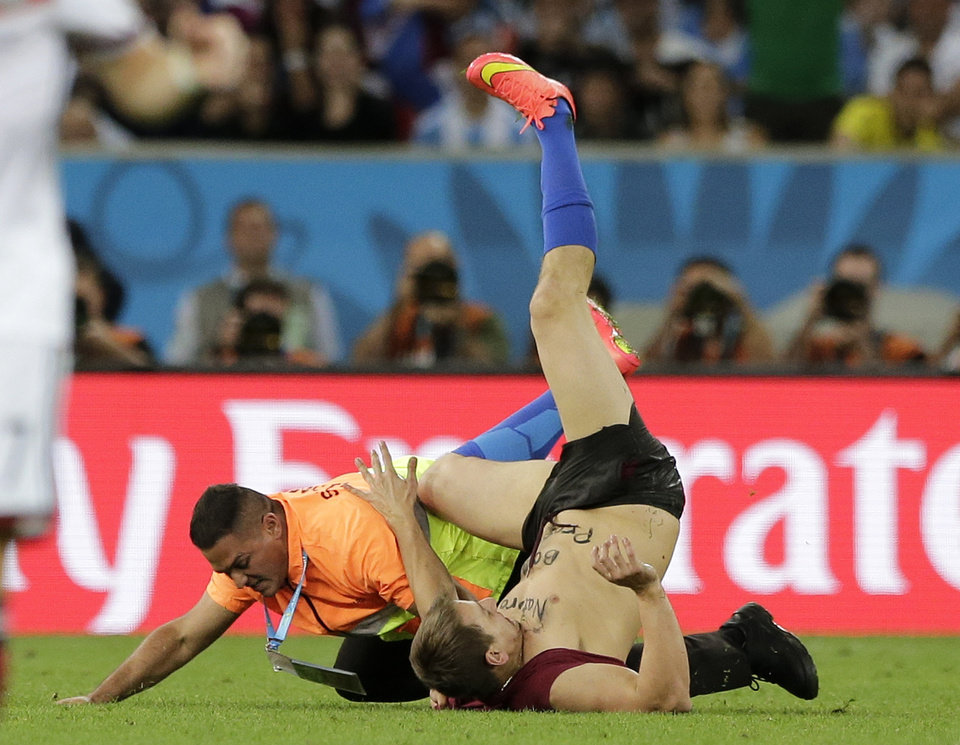 Photo - A steward apprehends a man who ran onto the pitch during the World Cup final soccer match between Germany and Argentina at the Maracana Stadium in Rio de Janeiro, Brazil, Sunday, July 13, 2014. (AP Photo/Matthias Schrader)