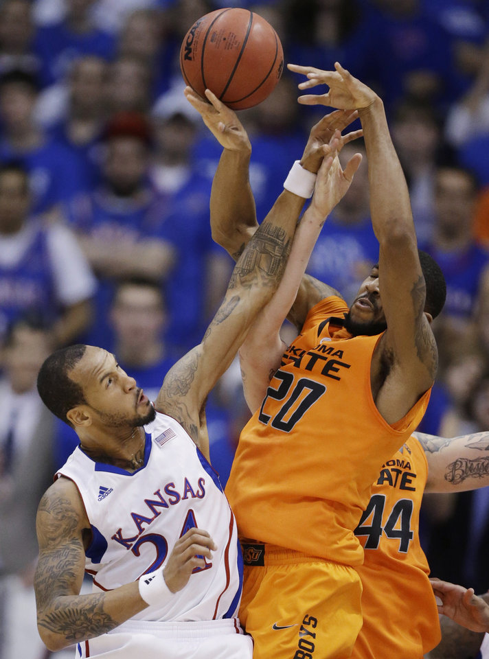 Kansas guard Travis Releford (24) reaches for a rebound next to Oklahoma State forward Michael Cobbins (20) and center Philip Jurick (44) during the first half of an NCAA college basketball game in Lawrence, Kan., Saturday, Feb. 2, 2013. (AP Photo/Orlin Wagner) ORG XMIT: KSOW106