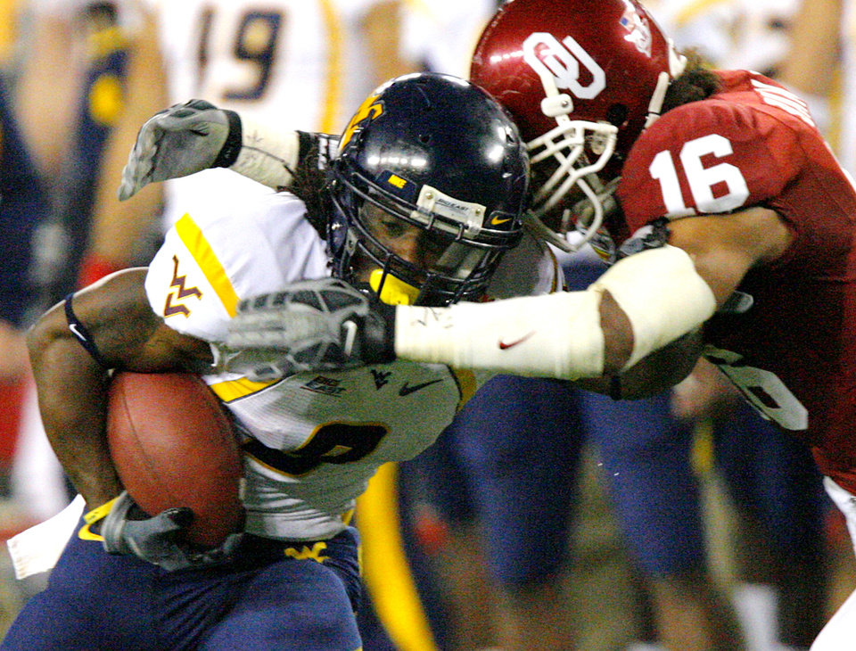 Photo - West Virginia's Jock Sanders (9) takes the ball against Oklahoma's Lewis Baker (16) during the first half of the Fiesta Bowl college football game between the University of Oklahoma Sooners (OU) and the West Virginia University Mountaineers (WVU) at The University of Phoenix Stadium on Wednesday, Jan. 2, 2008, in Glendale, Ariz. 