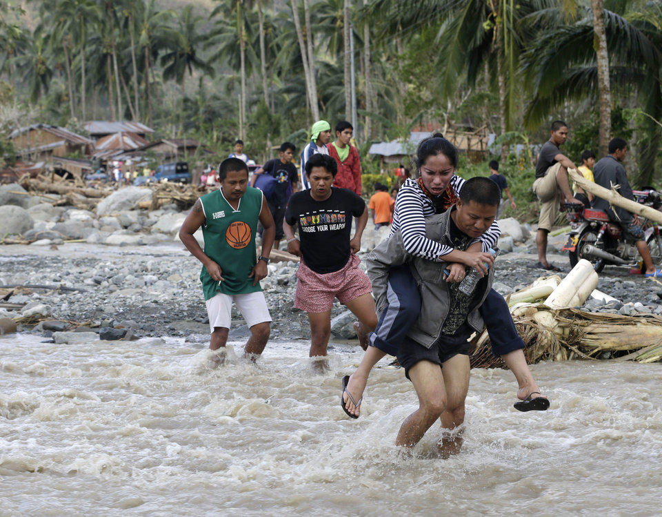 Photo - Residents cross a river at the flash flood-hit village of Andap, New Bataan township, Compostela Valley in southern Philippines Wednesday, Dec. 5, 2012.  Typhoon Bopha, one of the strongest typhoons to hit the Philippines this year, barreled across the country's south on Tuesday, killing scores of people and forcing more than 50,000 to flee from inundated villages. (AP Photo/Bullit Marquez)