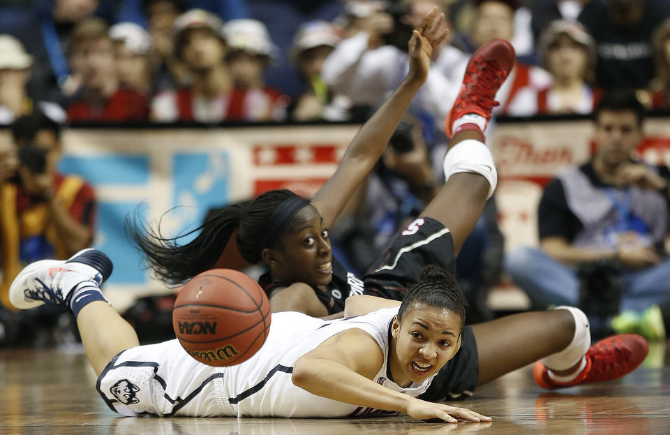 Photo - Stanford forward Chiney Ogwumike (13) and Connecticut guard Bria Hartley (14) collide during the second half of the semifinal game in the Final Four of the NCAA women's college basketball tournament, Sunday, April 6, 2014, in Nashville, Tenn. Connecticut won 75-56. (AP Photo/John Bazemore)