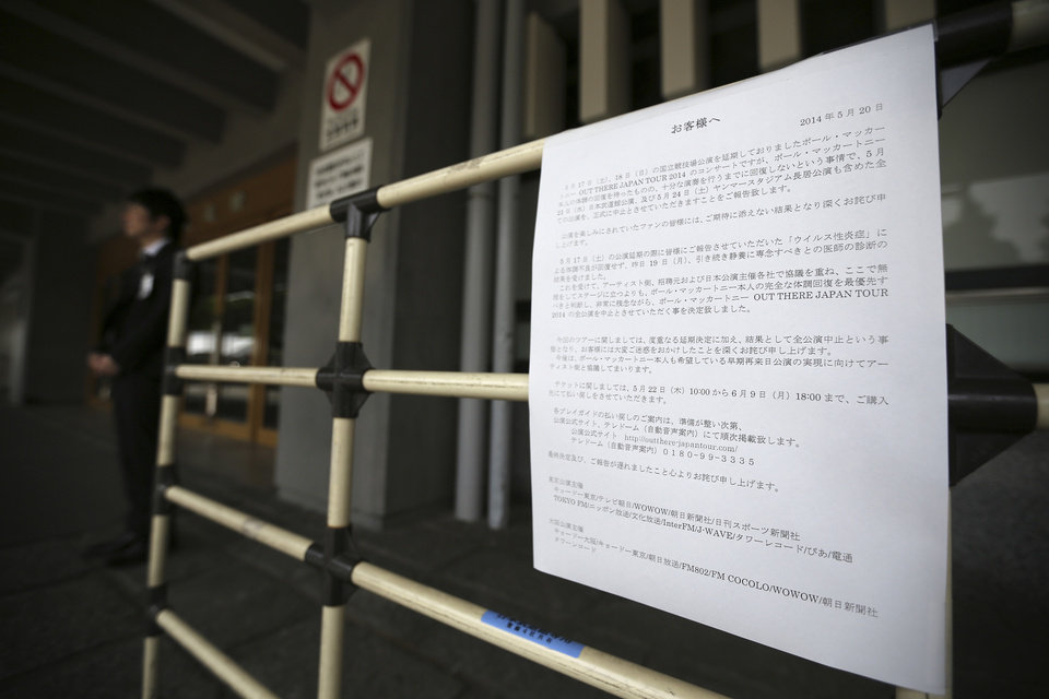 Photo - A man stands near a notice to fans announcing the cancellation of Paul McCartney's concert at Nippon Budokan hall in Tokyo, Tuesday, May 20, 2014. Paul McCartney is canceling his entire Japan tour because of illness including the one set for Wednesday at Nippon Budokan hall, where The Beatles performed during their first Japan tour in 1966. (AP Photo/Eugene Hoshiko)