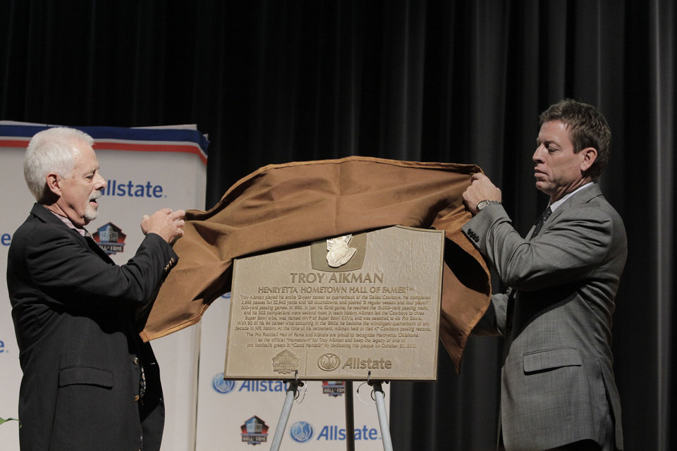 "Former high school football coach Rick Enis and pro football legend Troy Aikman unveil the historic Allstate Pro Football Hall of Fame ""Hometown Hall of Famers"" plaque at Henryetta High School today where the plaque will live to serve as an inspiration to future students and the Henryetta community. Photo courtesy of Allstate"