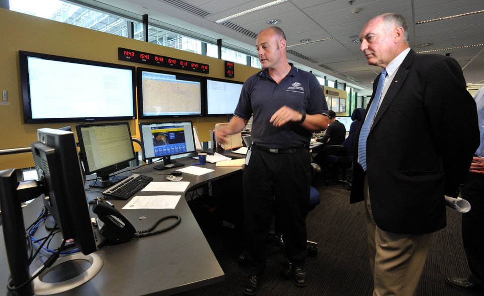 Photo - Australia's Deputy Prime Minister Warren Truss, right, and Dan Gillis, senior search and rescue officer involved in the search for the missing Malaysia Airlines Flight MH370, watch monitor at the Australian Maritime Safety Authority's rescue coordination center in Canberra, Sunday, March 23. 2014. Planes and ships scrambled Sunday to find a pallet and other debris in a remote patch of the southern Indian Ocean to determine whether the objects were from the Malaysia Airlines jet that has been missing for more than two weeks. (AP Photo/Graham Tidy, Pool)