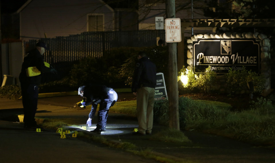 Photo - Police officers place evidence markers at the scene of an overnight shooting that left five people dead, Monday, April 22, 2013, at the Pinewood Village apartment complex in Federal Way, Wash. (AP Photo/Ted S. Warren)