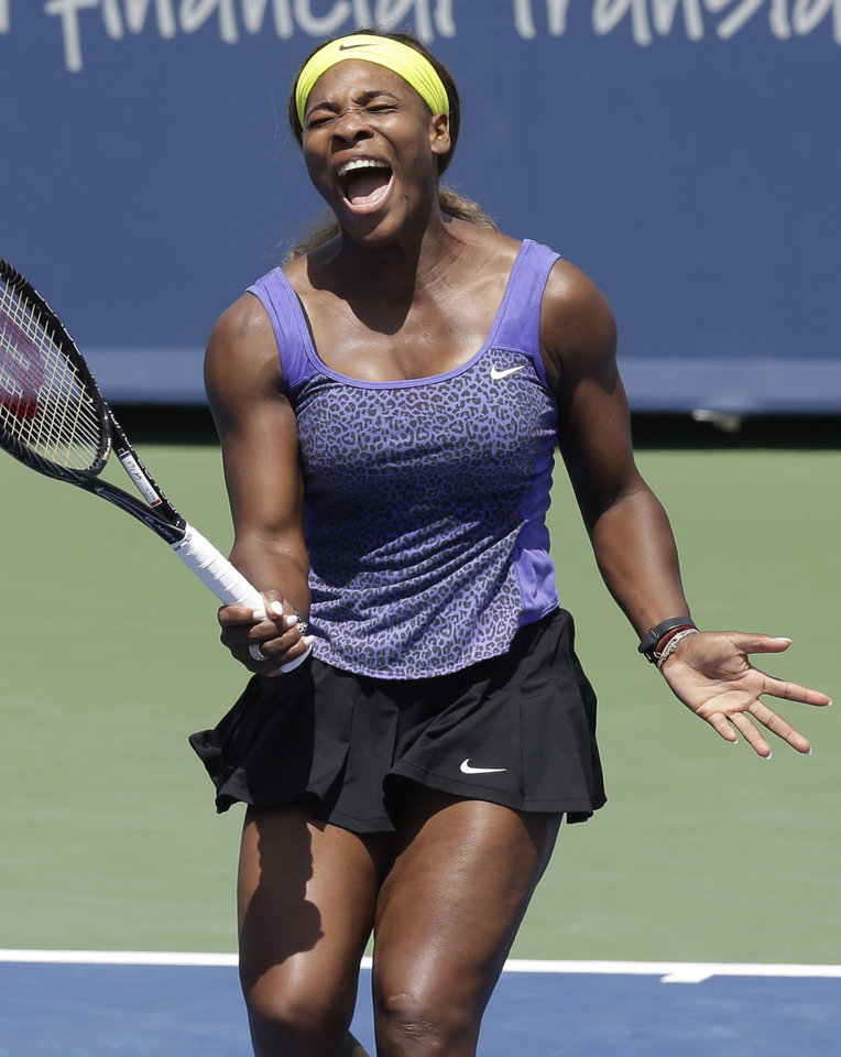Photo - Serena Williams reacts to a missed volley against Samantha Stosur, from Australia, during a match at the Western & Southern Open tennis tournament, Wednesday, Aug. 13, 2014, in Mason, Ohio. (AP Photo/Al Behrman)
