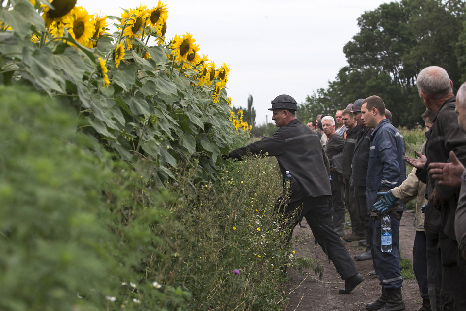 Photo - Ukrainian coal miners prepare to search the site of a crashed Malaysia Airlines passenger plane near the village of Rozsypne, Ukraine, eastern Ukraine Friday, July 18, 2014. Rescue workers, policemen and even off-duty coal miners were combing a sprawling area in eastern Ukraine near the Russian border where the Malaysian plane ended up in burning pieces Thursday, killing all 298 aboard. (AP Photo/Dmitry Lovetsky)
