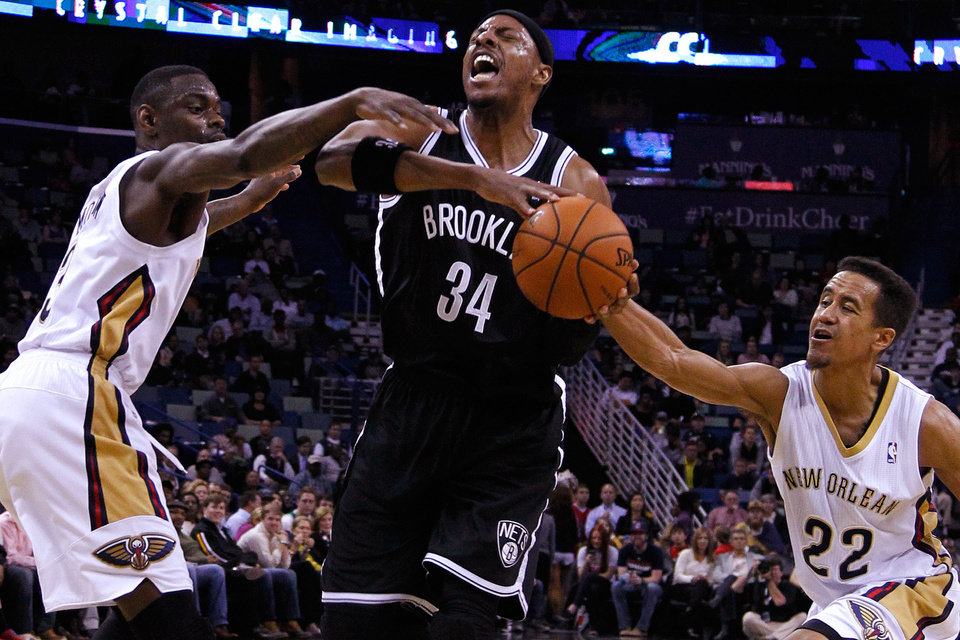 Photo - Brooklyn Nets forward Paul Pierce (34) drives against New Orleans Pelicans guard Anthony Morrow, left, and guard Brian Roberts (22) during the first half of an NBA basketball game in New Orleans, Monday, March 24, 2014. (AP Photo/Jonathan Bachman)