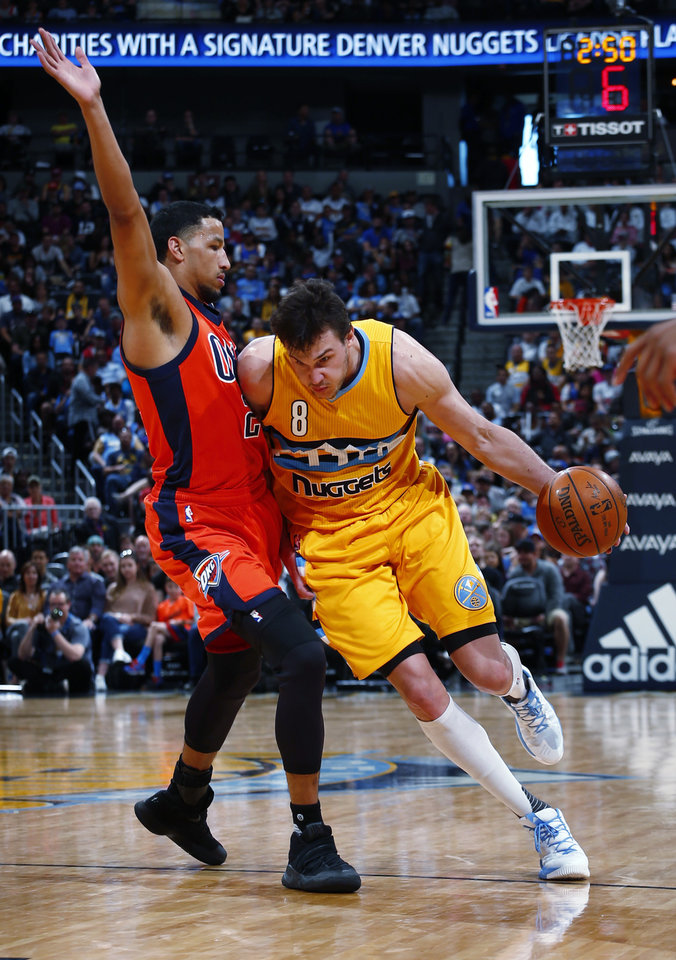 Photo - Denver Nuggets forward Danilo Gallinari (8) drives past Oklahoma City Thunder forward Andre Roberson (21) during the second half of a basketball game, Sunday, April 9, 2017, in Denver. (AP Photo/Jack Dempsey)