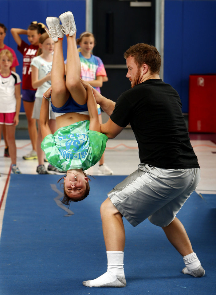 Photo - Instructor Morgan Bailey spots a jump by London Faulkner, 11, at a cheer and tumbling camp this week sponsored by Norman's Parks and Recreation Department. PHOTO BY STEVE SISNEY, THE OKLAHOMAN  STEVE SISNEY